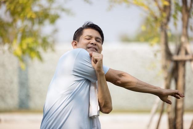 Sportmannen doen lichaam warming-up schouder arm strekken spier ontspannen voorbereiden op hardlopen en oefenen