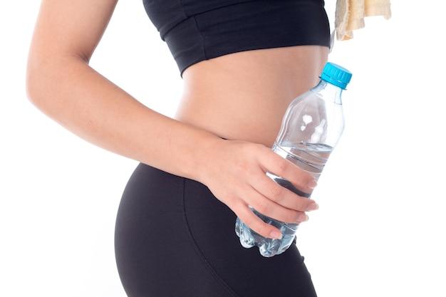 Sportmeisje dat een fles water in zijn handclose-up houdt
