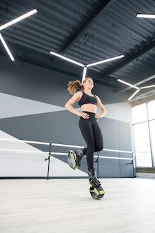 Sportmeisje dat kangoo-sprongen binnenshuis beoefent