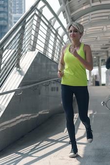 Sportmeisje die bij stad lopen