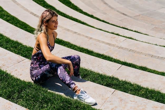 Sportmeisje ging zitten om te ontspannen op de trappen van het park in een vrije pose