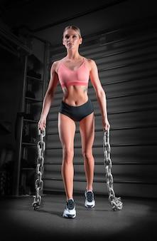 Sportmeisje traint in de sportschool tegen de achtergrond van de klimrekken. ze draagt zware metalen kettingen in haar handen. het concept van sport, fitness, aerobics, bodybuilding, stretching.