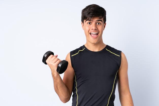 Sportmens die gewichtheffen over blauwe muur met verrassing en geschokte gelaatsuitdrukking maken
