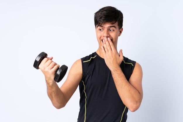 Sportmens die gewichtheffen over geïsoleerde blauwe achtergrond met verrassing en geschokte gelaatsuitdrukking maken