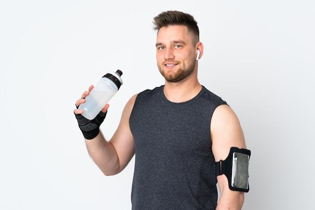 Sportmens op witte muur met de fles van het sportenwater wordt geïsoleerd die