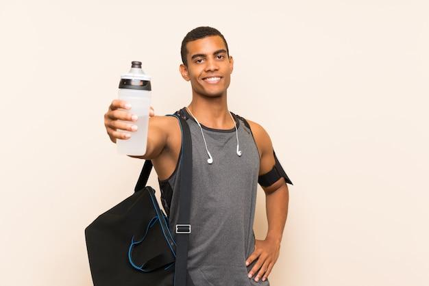 Sportmens over geïsoleerde achtergrond met een fles water