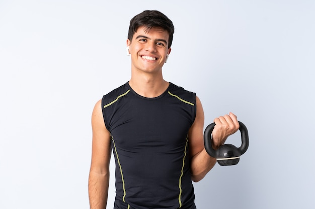 Sportmens over geïsoleerde blauwe achtergrond die gewichtheffen met kettlebell maken