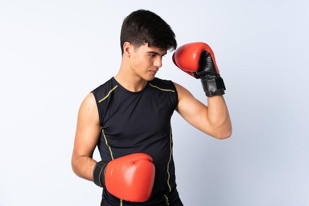 Sportmens over geïsoleerde blauwe achtergrond met bokshandschoenen