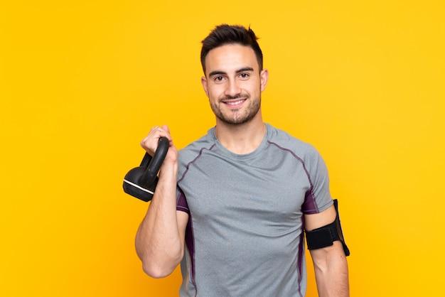 Sportmens over geïsoleerde gele muur die gewichtheffen met kettlebell maken