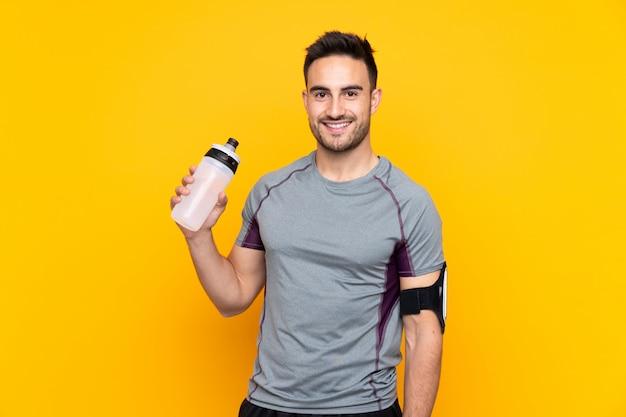 Sportmens over geïsoleerde gele muur met de fles van het sportenwater