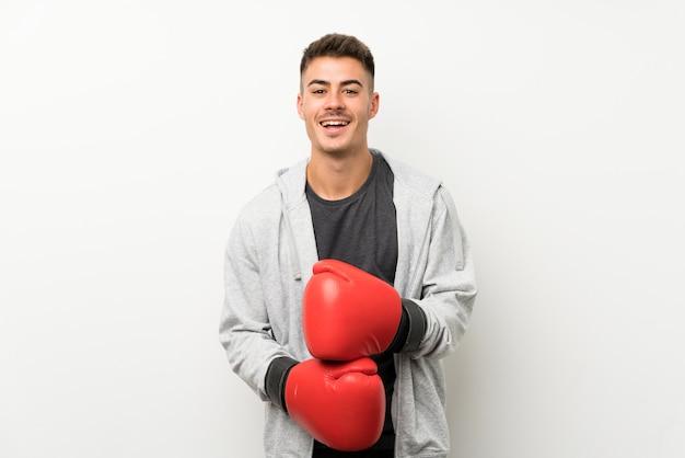 Sportmens over geïsoleerde witte muur met bokshandschoenen