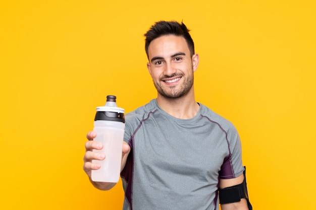 Sportmens over gele muur met de fles van het sportenwater