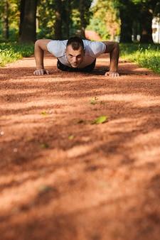 Sportmensen die opdrukoefeningen doen tijdens openlucht dwars opleidingstraining in het park