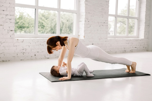Sportmoeder houdt zich bezig met fitness en yoga met een baby, doet plank- en push-ups op een zwarte mat