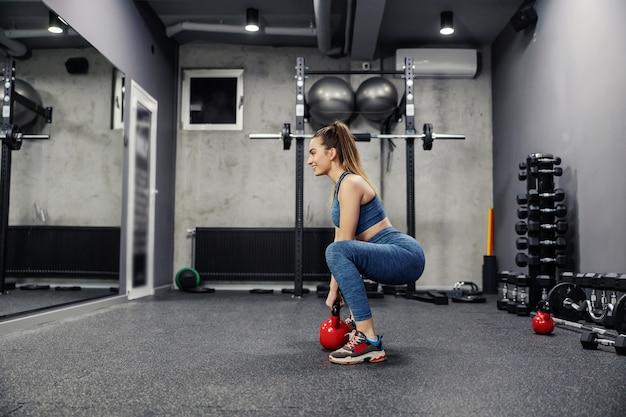 Sportoefeningen voor het leven en uithoudingsvermogen met ketelgewichten. zijaanzicht van een sexy vrouw in sportkleding en in goede vorm gewichtheffen in de sportschool. lichaamsstabiliteit, spierflexibiliteit en sportleven
