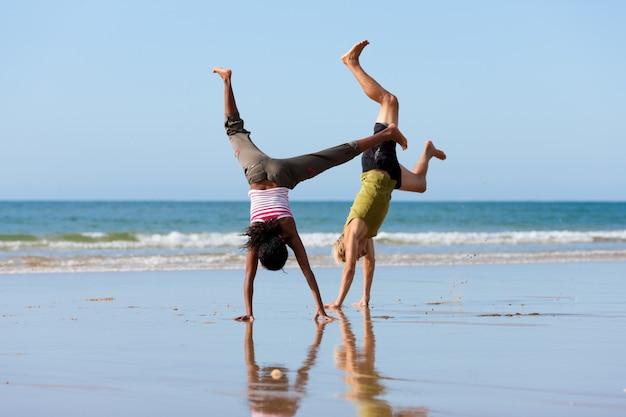 Sportpaar die gymnastiek op het strand doen