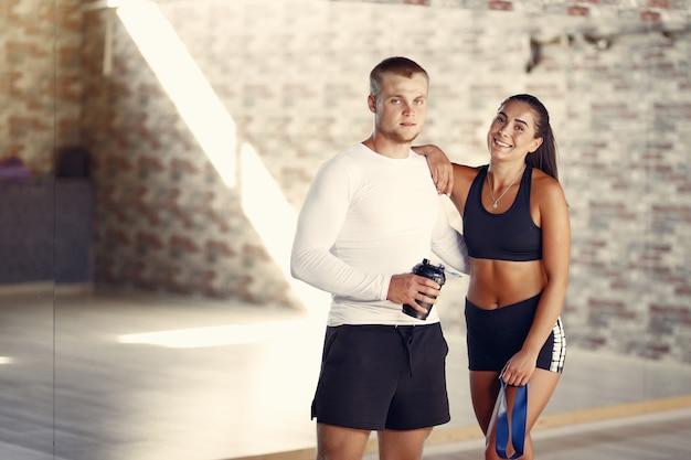 Sportpaar in sportkleding opleiding in een gymnastiek