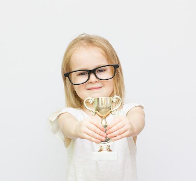 Sportprestaties. het meisje houdt een gouden beker. trots op haar prestatie.