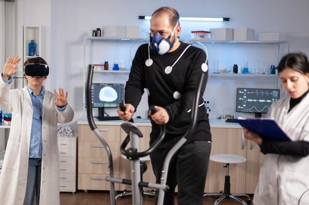 Sportprestatiewetenschapper die virtual reality-bril ervaart, atleet met elektroden die op cross-trainingstest lopen. uithoudingsvermogen meten met sensoren.