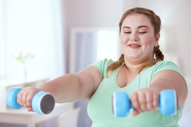 Sportprogramma. glimlachende jonge vrouw die oefeningen met halters doet tijdens het kijken naar sportprogramma