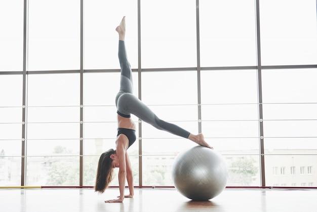 Sports is een mooie vrouw die yogalessen doet en haar benen strekt op de bal bij het grote raam
