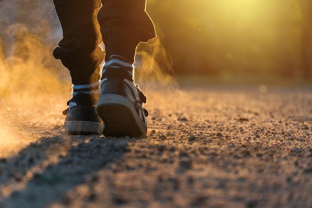 Sportschoenen. de jongen is geschoeid in gymschoenen en gestreepte sokken tegen de ondergaande zon. achteraanzicht.