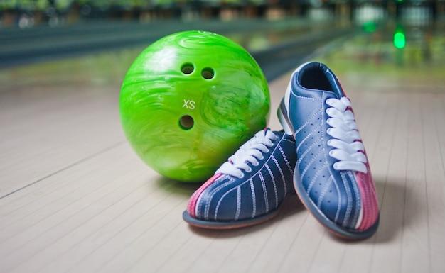 Sportschoenen en groene bal op vloer in kegelenclub