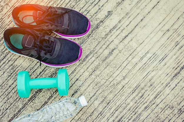 Sportschoenen met fles en groene kleurendomoor op de vloer