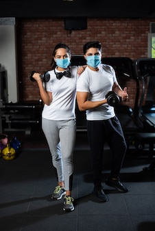 Sportschool na corona - indiaas jong stel traint in sportschool na corona-uitbraak, draagt beschermend gezichtsmasker
