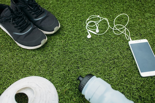 Sportset jongen of meisje, die graag rent. telefoon, koptelefoon, schoenen, bidon en chips voor hardlopen.