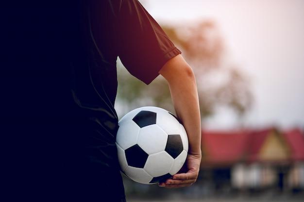 Sportspelers die de bal en het voetbalveld vangen.