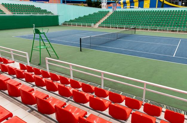 Sportstadion met verschillende rijen toeschouwersstoelen en een tennisbaan in een sportstadion of op een podium.