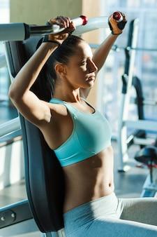 Sporttraining in de sportschool. aantrekkelijke jonge vrouw die geconcentreerd kijkt tijdens het sporten in de sportschool