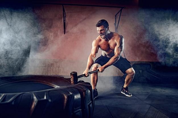 Sporttraining voor uithoudingsvermogen, man slaat hamer. concept training.