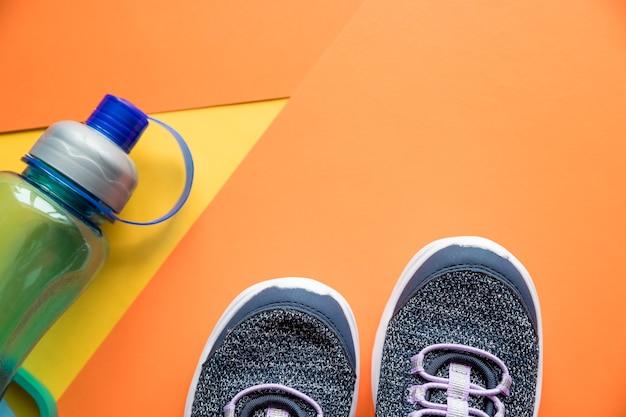 Sportuitrusting, blauwe sneakers, water, op oranje achtergrond, plat leggen. schoenen, springtouw en fles water
