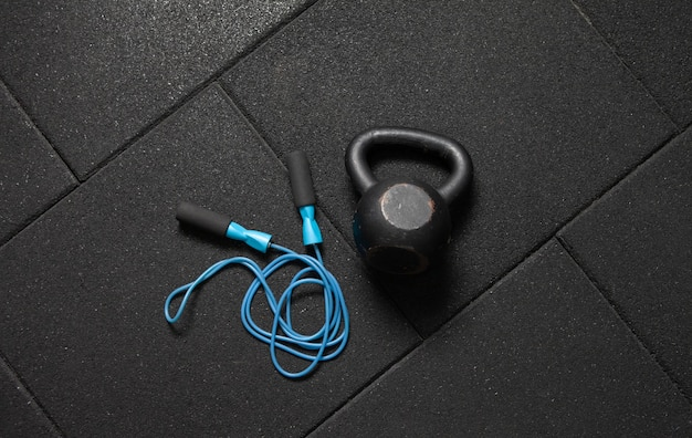 Sportuitrusting. kettlebell en springtouw op een donkere zwarte vloer. bodybuilding en fitness, functionele training