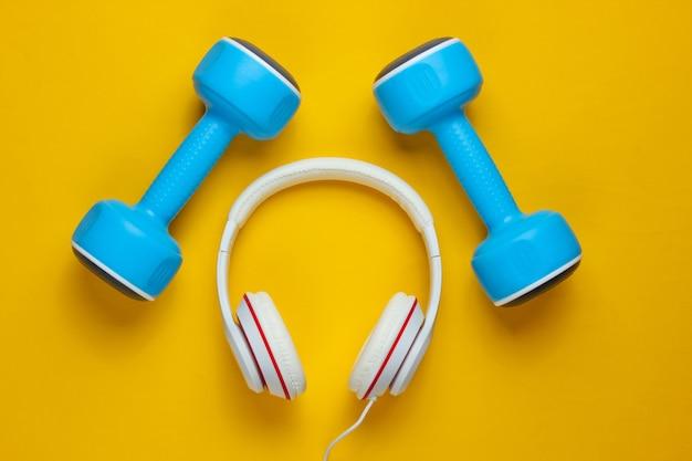 Sportuitrusting op gele achtergrond. sport levensstijl. halters, koptelefoons. fitness concept. bovenaanzicht, minimalisme, platliggend