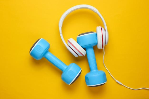 Sportuitrusting op gele achtergrond. sport levensstijl. halters, koptelefoons. fitness concept.