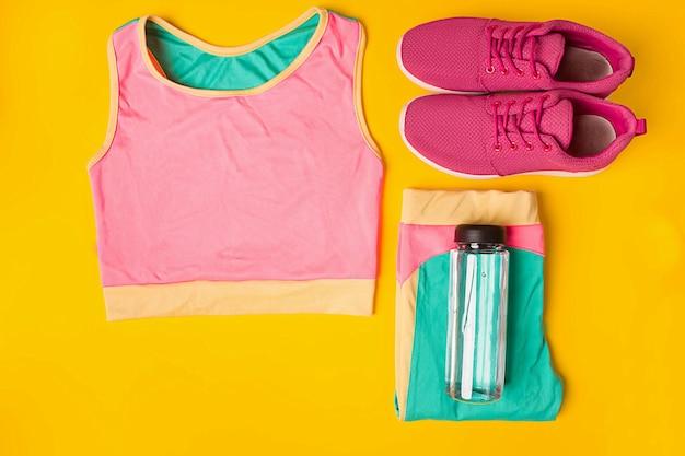 Sportuitrusting sneakers en fles water op gele achtergrond