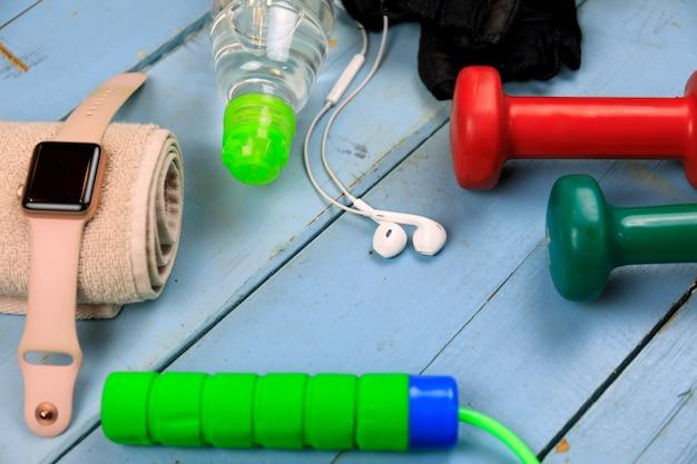 Sportuitrusting voor fitnesstraining. fles met water, slim horloge, oortelefoons en springtouw. instellen voor sportieve activiteiten.