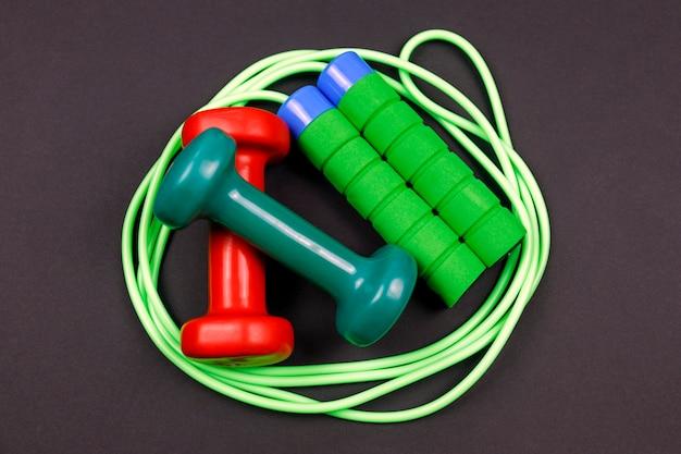 Sportuitrusting voor fitnesstraining op een zwarte. springtouw met halter.