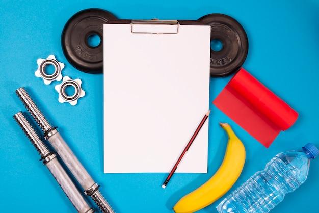 Sportuitrusting voor sport en fitness, bovenaanzicht, blauwe achtergrond, in het midden een papierhouder met lege witte vellen