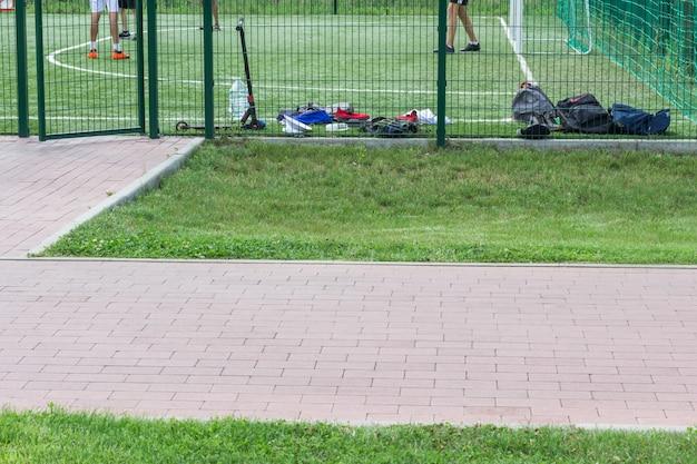Sportveld om te voetballen. rugzakken van spelers bij het hek, voeten van voetballers op het veld. ruimte kopiëren
