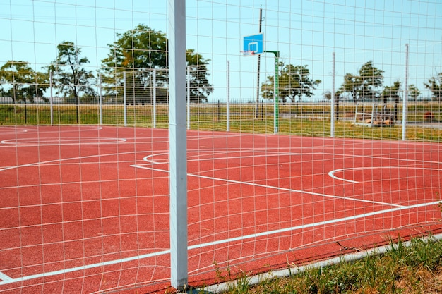 Sportveld voor kinderen en volwassenen. kunstgras. basketbalveld omheind met een hek.