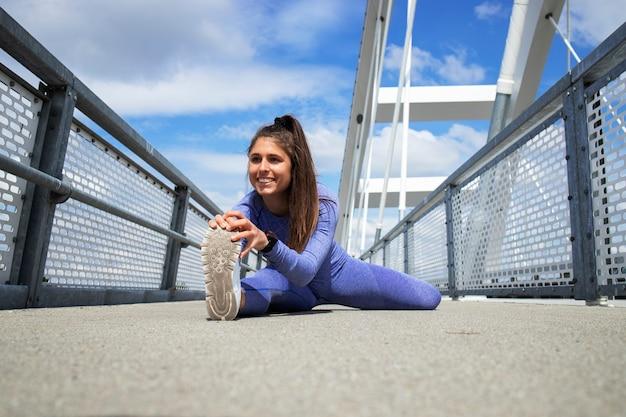 Sportvrouw benen strekken voor de training