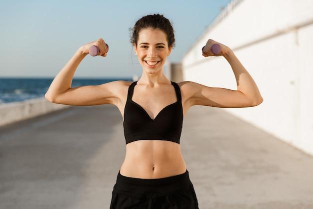 Sportvrouw die biceps buiten op het strand toont.