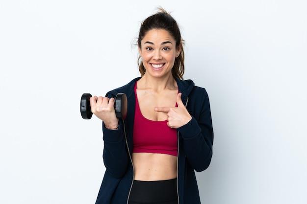 Sportvrouw die gewichtheffen over geïsoleerde witte muur met verrassingsgelaatsuitdrukking maken