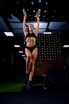 Sportvrouw die gymnastiekringen gebruikt
