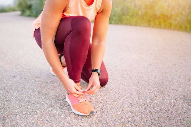 Sportvrouw die haar schoenveters bindt voor de training.