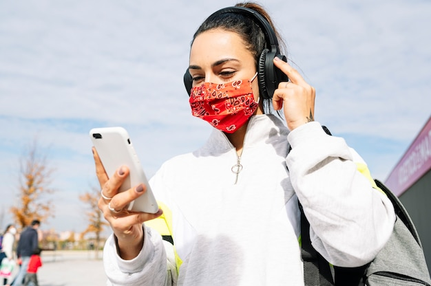 Sportvrouw die met masker aan muziek met hoofdtelefoons en slimme telefoon luistert